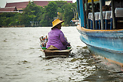 "17 NOVEMBER 2012 - BANGKOK, THAILAND:  A woman selling tourist curios approaches a tourist boat on the Chao Phraya River in Bangkok. Bangkok used to be known as the ""Venice of the East"" because of the number of waterways the criss crossed the city. Now most of the waterways have been filled in but boats and ships still play an important role in daily life in Bangkok. Thousands of people commute to work daily on the Chao Phraya Express Boats and fast boats that ply Khlong Saen Saeb or use boats to get around on the canals on the Thonburi side of the river. Boats are used to haul commodities through the city to deep water ports for export.    PHOTO BY JACK KURTZ"