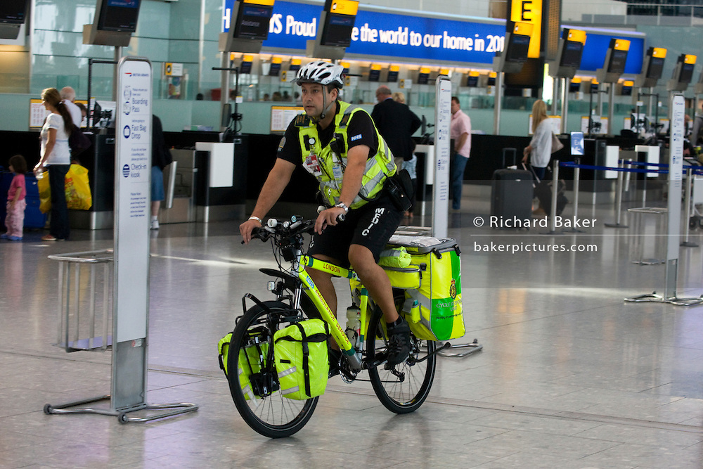 An NHS Paramedic Responder rides his 55kg Specialized Rockhopper mountain bike through in Heathrow's Terminal 5.