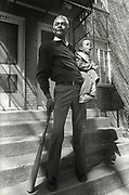 Israel Green leans on a baseball bat as he holds his grandson, two year old Taveris Green, Green. Green and a neighbor keep watch over their neighborhood at Atlanta's Techwood Homes public housing project. Armed with the bats, the two men hoped to keep the killer or killers of Atlanta's childern from their turf.