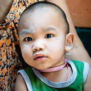 Portrait of mother holding baby in Khlong Toei neighbourhood of Bangkok