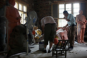 "Workers craft a statue of Mao Zedong out of resin at the workshop of a ""Red"" memorabilia collector and manufacturer, near Mao's birthplace in Shaoshan, Hunan Province, China on 12 August 2009.  The workers were once electricians.The village of Shaoshan, in rural Hunan Province, is tiny in size but big in name. It was the childhood home for Mao Zedong, the controversial revolutionary who came from obscurity but eventually defied all odds conquered China in the name of communism. Now his home, a sacred place among China's official propaganda, is in reality a microcosm of the country itself: part commercialism, part superstition, with a dash of communist ideological flavor."