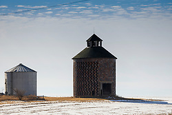 An old brick round storage bin sits alongside a newer steel one in the barn lot of a farmstead in rural Illinois