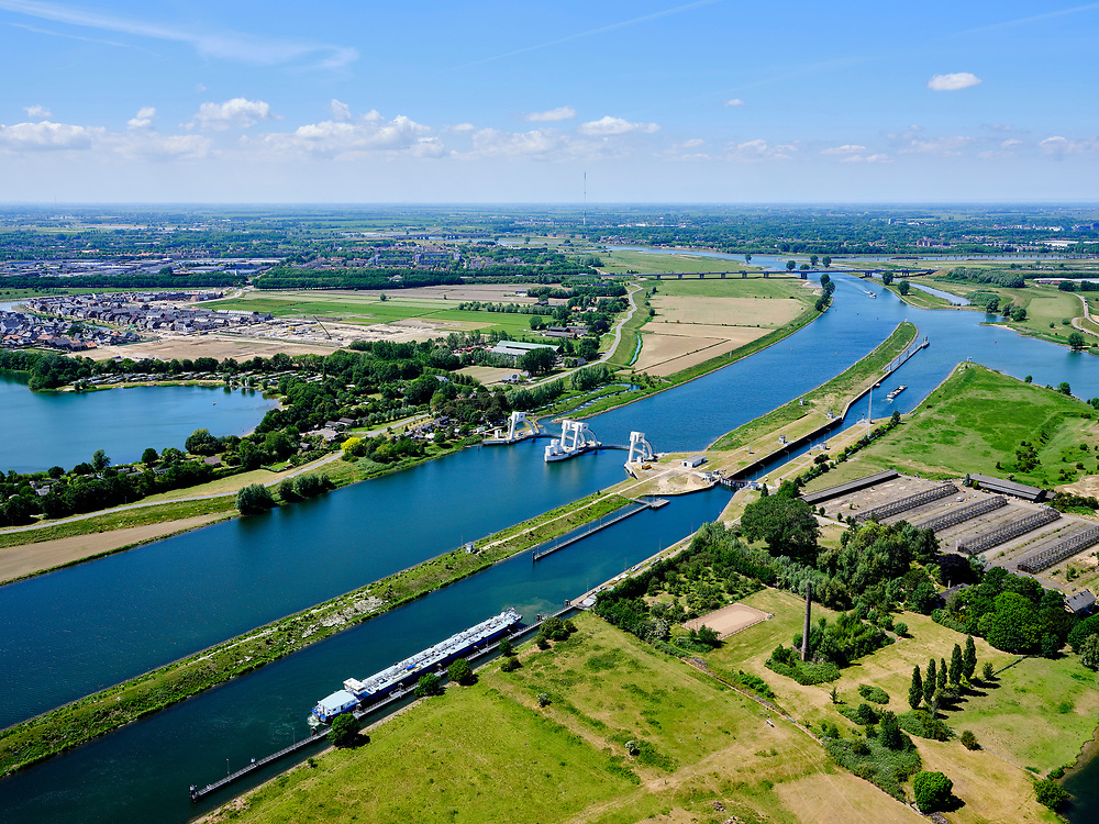 Nederland, Utrecht, Hagestein, 27-05-2020; stuw in de rivier de Lek, dient om het waterpeil in de rivier te reguleren en het scheepvaartverkeer mogelijk te maken. Het gehele stuwcomplex is gerenoveerd. Naast de stuw de schutsluis voor de scheepvaart,vissen kunnen gebruik maken van de de vistrap (vispassage).<br /> Weir in the river Lek, regulates and manages the water level. The Lek is a rain river, with especially in the winter large amounts of water (melt water), in the summer there is a shortage of water, the weir ensures sufficiently high water level for shipping. Next to the dam fish ladder and shipping lock. The complex has being renovated, the visor slides replaced.<br /> <br /> luchtfoto (toeslag op standard tarieven);<br /> aerial photo (additional fee required)<br /> copyright © 2020 foto/photo Siebe Swart