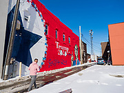 01 FEBRUARY 2020 - BOONE, IOWA: A man walks past a mural supporting President Donald Trump in downtown Boone, IA. Carl McKnight, a Boone realtor and Donald Trump supporter, commissioned the mural, which he calls nothing more than a campaign sign. Some in Boone, a community about 45 miles northwest of Des Moines, are concerned that the mural, which dominates a new park and bandshell in Boone, is not appropriate in a space shared by all people. A Boone city councilperson said people who donated to the fund to build the park have asked for their donations back. McKnight said the mural will stay up until at least election day.    PHOTO BY JACK KURTZ