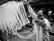 """29 DECEMBER 2018 - BANGKOK, THAILAND: A woman hangs longevity noodles out to dry in front of her family shophouse. The family has been making traditional """"mee sua"""" noodles, also called """"longevity noodles"""" for three generations in their home in central Bangkok. They use a recipe brought to Thailand from China. Longevity noodles are thought to contribute to a long and healthy life and  are served on special occasions, especially Chinese New Year, which is February 4, 2019. These noodles were being made for Chinese New Year.    PHOTO BY JACK KURTZ"""