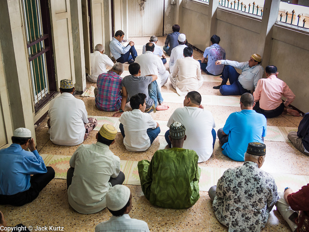 """08 AUGUST 2013 - BANGKOK, THAILAND: Men attend Eid al-Fitr services in a prayer room at Haroon Mosque in Bangkok. Eid al-Fitr is the """"festival of breaking of the fast,"""" it's also called the Lesser Eid. It's an important religious holiday celebrated by Muslims worldwide that marks the end of Ramadan, the Islamic holy month of fasting. The religious Eid is a single day and Muslims are not permitted to fast that day. The holiday celebrates the conclusion of the 29 or 30 days of dawn-to-sunset fasting during the entire month of Ramadan. This is a day when Muslims around the world show a common goal of unity. The date for the start of any lunar Hijri month varies based on the observation of new moon by local religious authorities, so the exact day of celebration varies by locality.      PHOTO BY JACK KURTZ"""