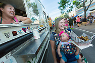 Sheryl Barham and her daughter Hattie, 4-months-old, receive an order of french fries from Janet Payne, owner of the Green Chile Paddy Wagon, on Wednesday, May 11, 2016, during the first evening of the Las Cruces Farmers and Crafts Market.