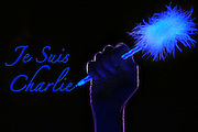 """Hand holding a glowing pen next to """"Je Suis Charlie"""" text.Black light"""