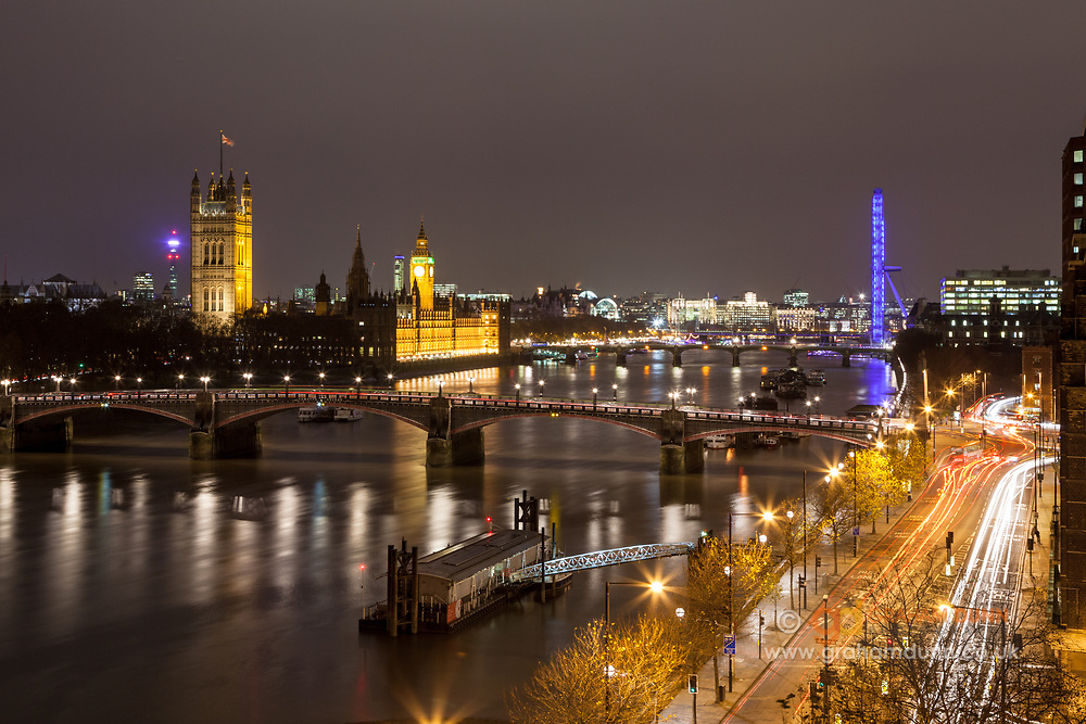 The Houses of Parliament, Big Ben, The London Eye amongst other wonders of the London skyline as seen from an elevated viewpoint on Albert Embankment. Lambeth Bridge can be seen crossing the River Thames in the foreground. A nighttime cityscape of our capital city in England, UK.