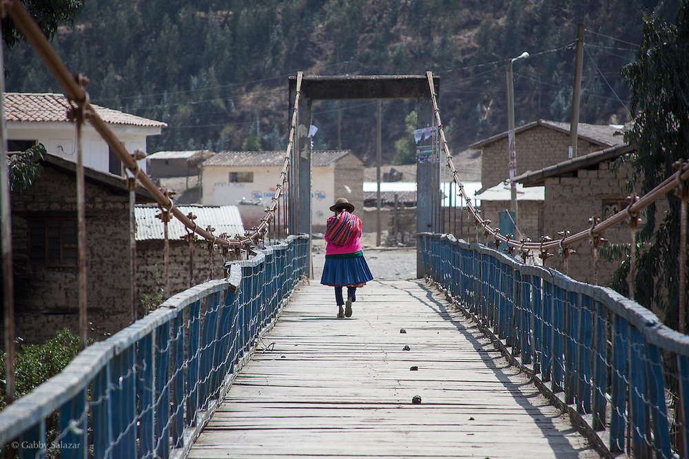 Andean woman walks on bridge in the village of Sunchubamba, a Quechua speaking native community in Southeastern Peru that is running a reforestation plot in the Andes near Cusco and the Interoceanic Highway.