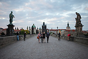 Early morning visitors on Prague Charles Bridge - view to Prague Old Town during the early morning change from night to day.