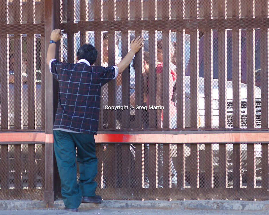 Man speakes to his family at the US-Mexican Border, Calexico, California