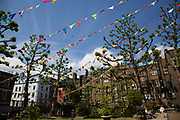Summertime in London, England, UK. Bunting up in preparation of a fete in the park outside Saint Anne's Church in Soho. The churchyard around the tower and west end are now the public park of St Anne's Gardens