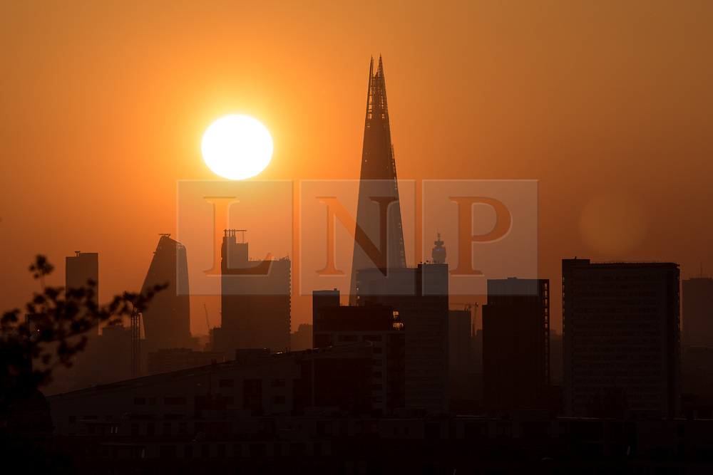 © Licensed to London News Pictures. 05/05/2018. London, UK. The sun sets over the London skyline, as seen from Greenwich Park. The warm weather over this bank holiday is forecast to peak on Monday, and is set to be the warmest on record. Photo credit : Tom Nicholson/LNP