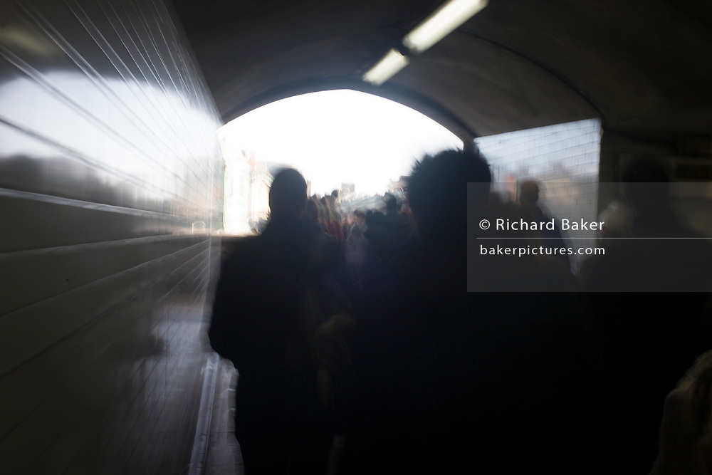 Blurred people walk towards bright sunlight through a subway tunnel beneath the Embankment in central London.
