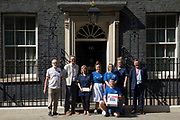 NHS workers from the grassroots NHSPay15 campaign, supported by former Labour Party leader Jeremy Corbyn and MPs Lloyd Russell-Moyle and Ian Byrne, pose outside 10 Downing Street before presenting Matthew Toveys petition signed by over 800,000 people calling for a 15% pay rise for NHS workers on 20th July 2021 in London, United Kingdom. At the time of presentation of the petition, the government was believed to be preparing to offer NHS workers a 3% pay rise in recognition of the unique impact of the pandemic on the NHS.