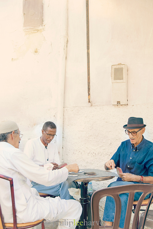 Three senior men sitting by small table and playing cards outside cafe in medina, Casablanca, Morocco