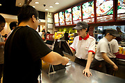 People in a fast food restaurant inside Joy City Shopping Mall. Xidan is one of the main commercial shopping area in the Xicheng district of Beijing, China. With Joy City as it's centerpiece, a 13-story complex of western and Chinese shops. This is a shoppers haven as modern consumerism and commerce have a strong grip on Beijing's shop hungry crowds.