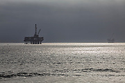 Oil Derrick and surfers off coast of Huntington Beach, Orange County, California, USA