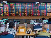 08 JULY 2015 - BANGKOK, THAILAND: People watch Thai stocks at a brokerage house in Bangkok. Thai financial markets and the Thai Baht both lost value Wednesday. The stock market, the Stock Exchange of  Thailand (SET) closed at 1,470.25, down 13.52 or 0.91%, from Tuesday. The Thai Baht closed at 33.90 Baht to 1 US Dollar, it's lowest point since September 2009. Economists blamed the drop in the Chinese stock markets and uncertainty over the EU's handling of the Greek budget crisis for the drops in Thai markets.    PHOTO BY JACK KURTZ