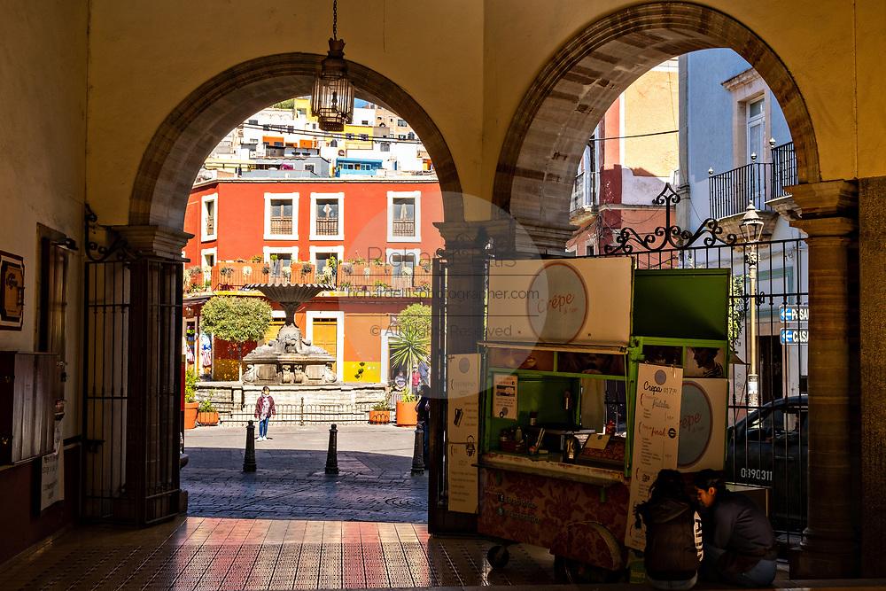 A view from an arcade of the Plaza Baratillo and fountain balcony in the historic center of Guanajuato City, Guanajuato, Mexico.