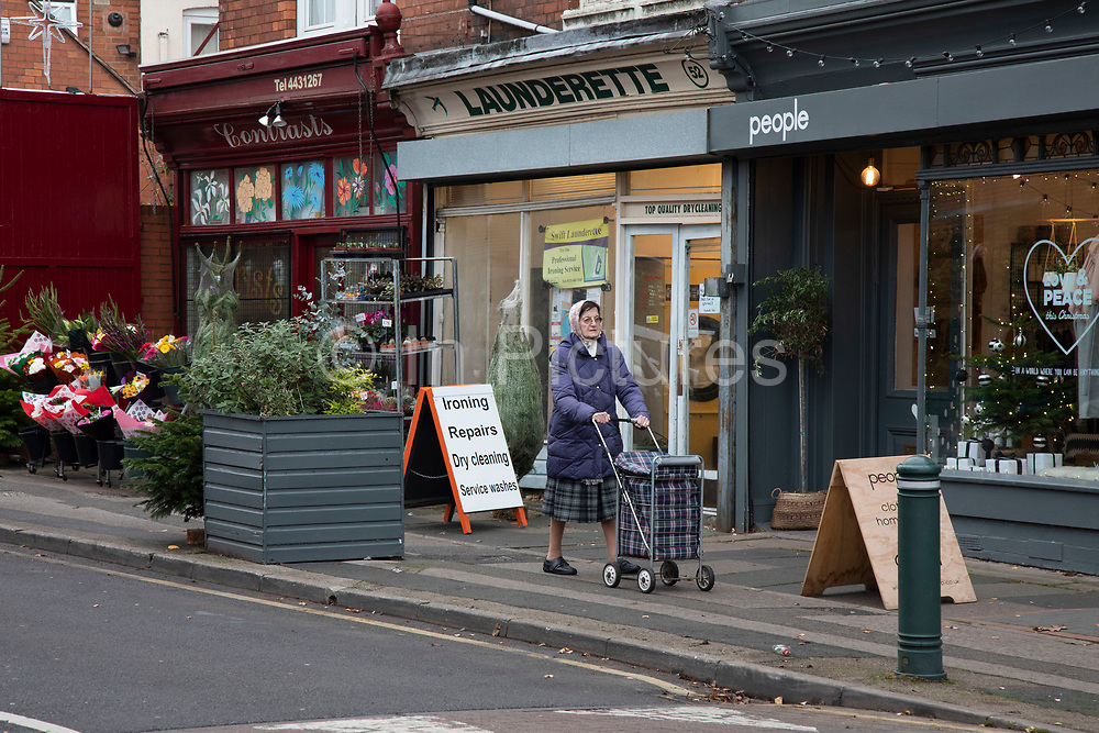 Street scene  of an edlerly woman pushing her shopping trolley past shops in Moseley / Kings Heath in Birmingham, United Kingdom.