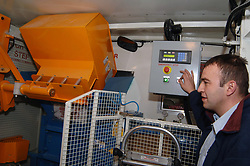 A man operates a mobile paper shredder on a lorry which collects confidential waste from offices to recycle