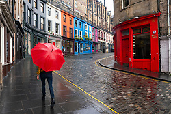 Edinburgh, Scotland, UK. 29 June, 2020. Many shops which have door access to the street are allowed to open for business in Scotland today. Despite cool temperatures, high winds and often heavy rain, some shops had queues outside in the morning. Tourist shops on the Royal Mile remained closed however, due to a lack of tourists,  and streets in the Old Town remained empty.  Pictured; Lone member of public walks in rain on Victoria Street with most tourist shops still closed.  Iain Masterton/Alamy Live News