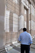 In the week that many more Londoners returned to their office workplaces after the Covid pandemic, a City worker stands beaneath sun reflections on the walls of the Bank of England in the City of London, the capital's financial district, on 8th September 2021, in London, England.