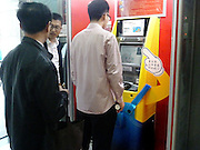 NANJING, CHINA - NOVEMBER 16: (CHINA OUT) <br /> <br /> A face you can bank on: China launches the country's first cash machines using facial recognition technology<br /> <br /> China could soon wave goodbye to bank cards as it rolls out the first of its facial recognition enabled ATMs.<br /> The clever machines were recently made available to customers of China Merchants Bank in the cities of Shenzhen, Nanjing and Qingdao, with more planned for the future.<br /> It is the first time the technology has been made available for public use in China since the technology was unveiled earlier this year<br /> A total of 10 facial recognition ATMs were introduced to China Merchant Bank branches in cities around the country this month - the first of its kind in the country.<br /> Some of the machines were Minions-themed while others were plain.<br /> They allow users to access their bank accounts by scanning their faces, effectively making bank cards redundant.<br /> There are obvious security concerns over the use of the machines and as an added security, users must input their telephone numbers as well as a password.<br /> Staff claims that the machine is even able to distinguish between twins as the visual image processing technology used takes its profile from several parts of the face.<br /> <br /> This has been successfully proved during the product testing stage of the machine.<br /> They also claim a small variation in appearance, including wearing glasses or make-up, shouldn't affect the efficiency of the system.<br /> However, major plastic surgery would require customers to update their photograph used on their identification cards.<br /> The technology eliminates the use of cards. With the average speed of a cash withdrawal reportedly just 42 seconds, it could also speed up the process.<br /> However, users are restricted to a daily withdrawal limit of 3,000 Yuan (£300), compared to conventional methods that allow users to withdrawn up to 20,000 Yuan (£2,000).<br