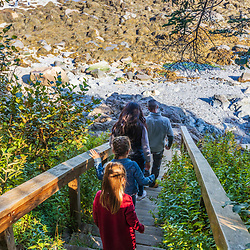 A couple and their two daughters explore a rocky beach at Quoddy Head State Park in Lubec, Maine.