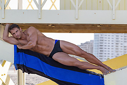 handsome man in a speedo under a lifeguard stand