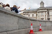 Tourists and incongruous traffic cones on the steps outside the National Gallery in Trafalgar Square, on 15th June 2019, in London, England.