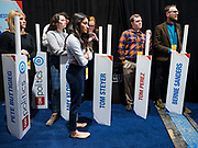 14 JANUARY 2020 - DES MOINES, IOWA: Debate volunteers wait to go into the spin room with placards for the candidates near the end of the CNN Democratic Presidential Debate on the campus of Drake University in Des Moines. This is the last debate before the Iowa Caucuses on Feb. 3.    PHOTO BY JACK KURTZ