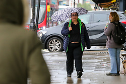 © Licensed to London News Pictures. 28/04/2021. London, UK. A woman shelters from the rain beneath an umbrella as rain starts to fall in north London for the first time in days.  Photo credit: Dinendra Haria/LNP