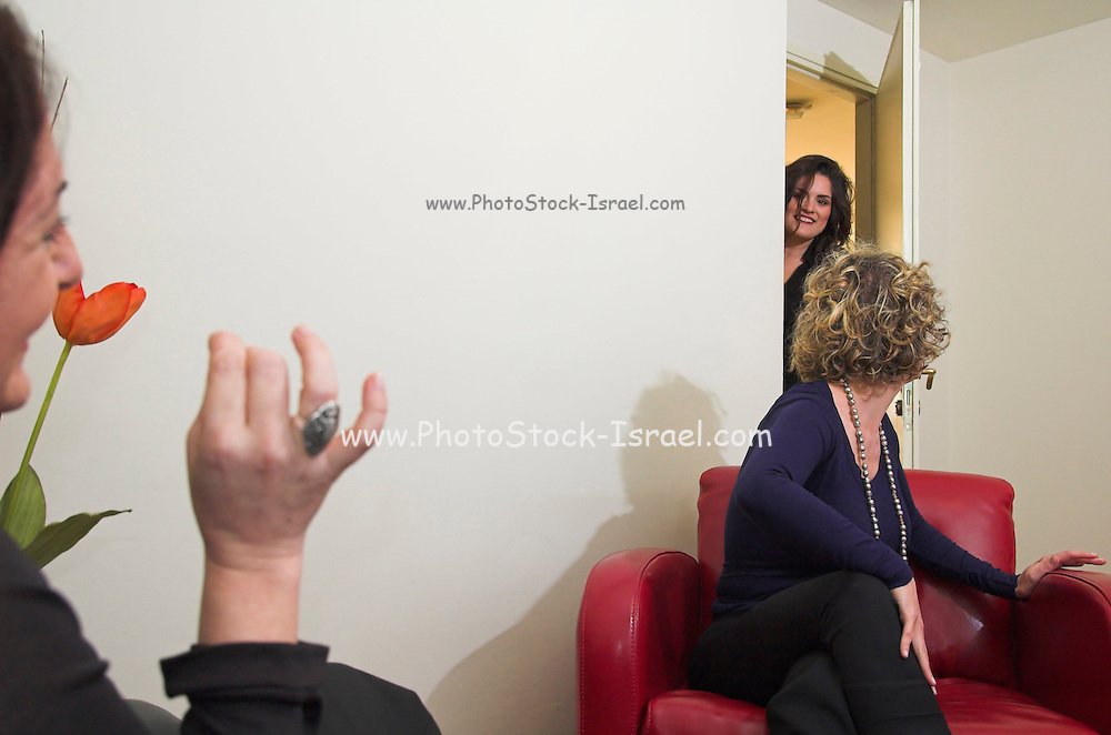 A female therapist during a one on one session with a client seeking help, session being interrupted by the secretary