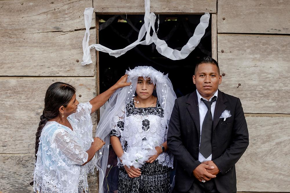 Una boda Maya. Los novios Gladis Rash, 18, y Alexander Caal, 22, posan para un retrato mientras la señora Rash le acomoda el velo a su hija en la comunidad Las Muñecas, Ixcan, Guatemala. 30 de Junio, 2019. Fred Ramos para El Faro y El País.