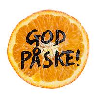 Påskehilsenen «God påske!» skrevet på en skåret appelsin, isolert mot hvit bakgrunn.