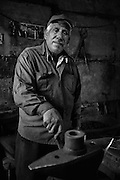 A blacksmith standing in his shop in the Roma ghetto of Stolipinovo in Plovdiv, Bulgaria