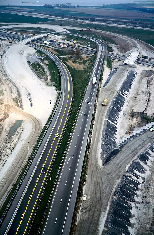 Nederland, Brabant, knooppunt Klaverpolder, 04-04-2002; het verkeersplein Klaverpolder wordt gereconstueerd omdat de A16 (Breda-Dordrecht, van links naar rechts) verbreed wordt en 2x3 rijstroken krijgt; de A59 (vanuit Roosendaal) in de voorgrond, water Hollandsch Diep id achtergrond; asfalt, automobiliteit, filebestrijding, autosnelweg, verkeer en vervoer,  bouw.<br /> luchtfoto (toeslag), aerial photo (additional fee)<br /> photo/foto Siebe Swart