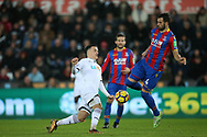 Roque Mesa of Swansea city (l) challenges Luka Milivojevic of Crystal Palace. Premier league match, Swansea city v Crystal Palace at the Liberty Stadium in Swansea, South Wales on Saturday 23rd December 2017.<br /> pic by  Andrew Orchard, Andrew Orchard sports photography.