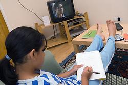 Girl doing her homework whilst watching TV,