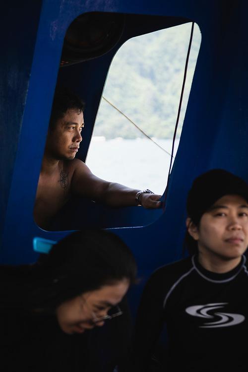 Coron, Philippines - July 20, 2019: Rodnie N. Tabangay at the helm of his boat which carries tourists on day trips to various beaches and other locations around Coron.