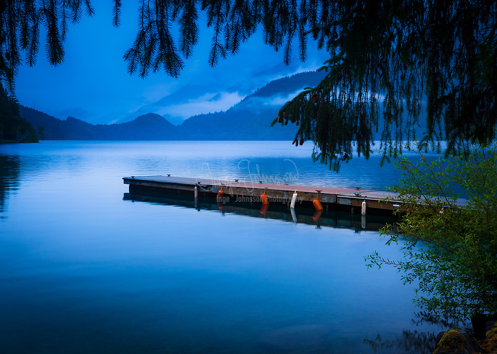 """Lake Crescent is a deep lake located entirely within Olympic National Park in Clallam County, Washington, United States, approximately 17 miles west of Port Angeles, Washington on U.S. Route 101 and nearby to the small community of Piedmont. At an official maximum depth of 624 feet it is officially the second deepest lake in Washington. Unofficial depth measurements of more than 1,000 feet have been recorded. Lake Crescent is known for its brilliant blue waters and exceptional clarity, caused by a lack of nitrogen in the water which inhibits the growth of algae. It is located in a popular recreational area which is home to a number of trails, including the Spruce Railroad Trail, Pyramid Mountain trail, and the Barnes Creek trail to Marymere Falls. The Spruce Railroad Trail follows the grade of what was once the tracks of a logging railroad along the shores of the lake. Following this trail on the north side of the lake, one can find the entrance to an old railroad tunnel as well as """"Devils Punch Bowl"""", a popular swimming and diving area."""