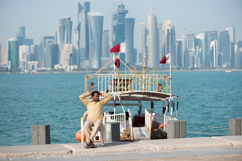 A man sits outside a dhow, waiting for tourists who may want a ride around the harbor, in Doha, Qatar