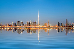Skyline of towers reflected in the Creek at dawn in Business Bay  in Dubai United Arab Emirates