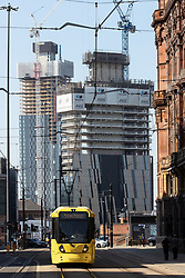 "© Licensed to London News Pictures . 19/05/2018. Manchester, UK. A tram running along Lower Mosley Street towards St Peter's Square in Manchester City Centre with developments on Deansgate Locks and one of Manchester's "" Twin Towers "" in the Deansgate Quay area in the background . Photo credit: Joel Goodman/LNP"