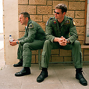 Two RAF fighter pilots listen to a pre-flight-briefing by the leader of the 'Red Arrows', Britain's Royal Air Force aerobatic team whose elite ranks these two men want to join. The candidates are with others and are in Cyprus during the team's training programme to be tested though only three new members are selected each year. They will have accumulated over 1,500 flying hours in fast jets with experience in theatres of war. If successful, they will spend three years in the Red Arrows then return to frontline and instructing duties. Since 1965 the squadron have flown over 4,000 shows in 52 countries. During a forthcoming calendar of appearances at air shows and fly-pasts across the UK and a few European venues they are an important recruiting tool for future personnel – of pilots and ground-based trades.