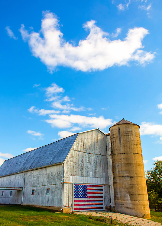 A great old barn and silo under blue skies and a prominent American Flag Painted On The Door