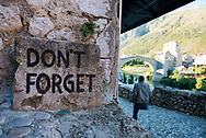 """An amputee walks past a sign that reads, """"Don't Forget"""", a reminder of the destructive war and seige that Mostar endured the the Bosnian war in the 1990s. In the background is the famous Old Bridge, or Stari Most, which was destroyed during the war and then rebuilt."""